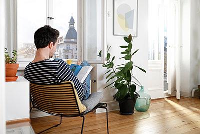 Man sitting at home, using laptop - p300m1587638 von Florian Küttler