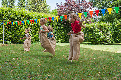 Children having a sack race in garden on a birthday party - p300m838590f by Nico Hermann