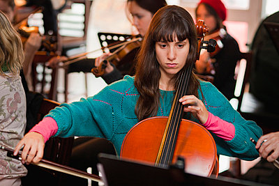 Cello player practicing with group - p429m712174f by Hybrid Images