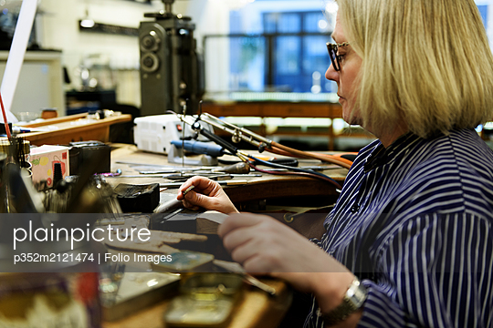 Goldsmith working on ring - p352m2121474 by Folio Images
