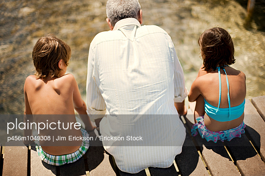 Old grandfather sitting with his two young grandchildren on a wooden jetty at the beach - p456m1049308 by Jim Erickson / Erickson Stock