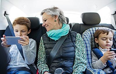 Senior woman looking at grandson using smart phone in car - p1166m1145259 by Cavan Images