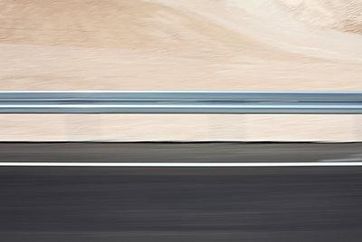 Highway in the desert with side strip and crash barrier - p1685m2272447 by Joy Kröger