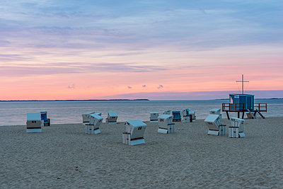 Germany, North Frisia, Sylt, Hoernum, beach with hooded beach chairs at sunrise - p300m1499215 by Kerstin Bittner