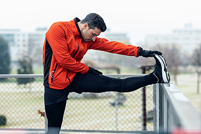 Male athlete touching toe while leg on chainlink fence at park - p300m2275558 by Josep Suria