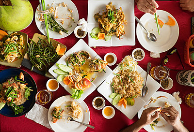 Overhead view of seafood and salad dishes on table - p555m1411744 by Roberto Westbrook