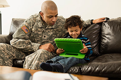 Mixed race soldier father and son using digital tablet on sofa - p555m1412423 by Roberto Westbrook