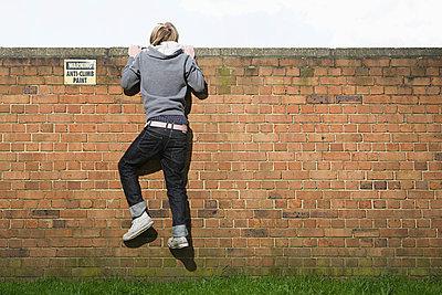 Teenage boy climbing wall - p9248763f by Image Source