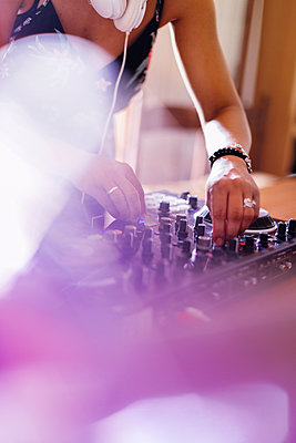 Midsection of female DJ mixing sound on table in recording studio - p1166m2034424 by Cavan Images