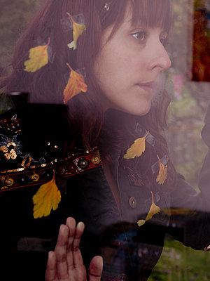 Woman looks through a windowpane - p1279m2134039 by Ulrike Piringer