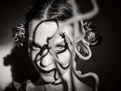 Frau mit Zweig vor dem Gesicht, Lichterspiel - p1413m2215620 von Pupa Neumann