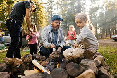 Family with three girls (2-3, 4-4, 6-7) roasting marshmallows above campfire, Wasatch-Cache National Forest - p1427m2213549 by Jessica Peterson