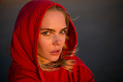 Portrait of young woman wearing red hooded jacket in evening light - p300m2029451 by Jean Schwarz
