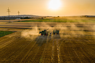 Aerial view of combine harvester on agricultural field against sky during sunset - p300m2143427 by Martin Moxter