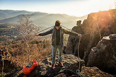 Female climber with rope standing on Battert rock at sunset, Baden-Baden, Germany - p300m2160227 von Manuel Sulzer