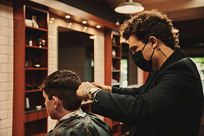 Male hairdresser cutting hair of customer in salon during COVID-19 - p300m2287165 by Aitor Carrera Porté