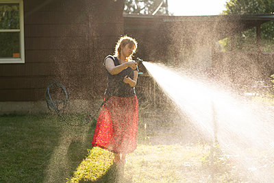 Woman spraying garden with water from garden hose - p924m1422775 by Raphye Alexius