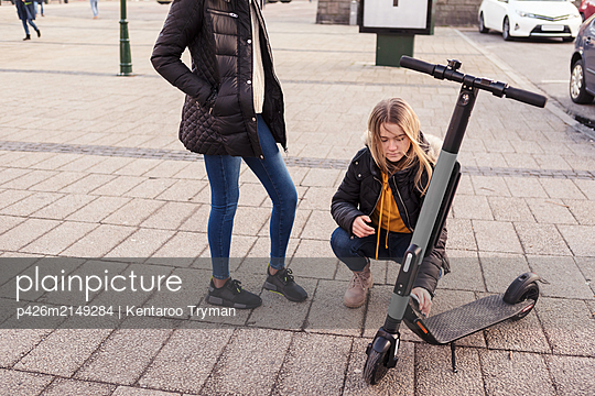 Teenage girl scanning mobile phone over electric push scooter while crouching by friend on city street - p426m2149284 by Kentaroo Tryman