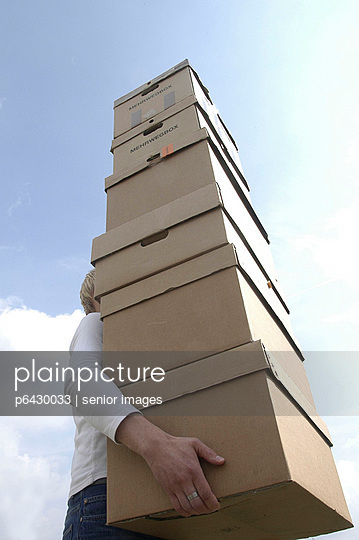 Mann traegt einen grossen Stapel Kartons  - p6430033 von senior images