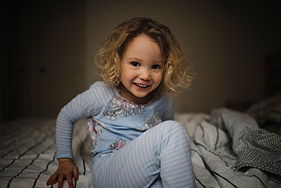 Portrait of smiling girl sitting on bed at home - p1166m1575940 by Cavan Social
