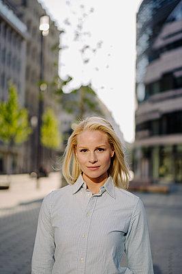 Confident beautiful blond businesswoman standing in city - p300m2214098 by Joseffson