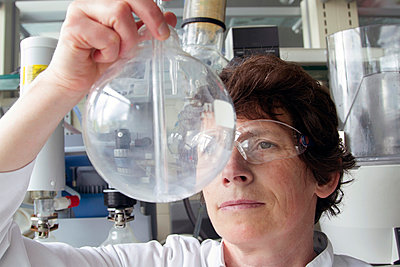 Female chemist looking at round-bottom flask in laboratory - p300m950688f by Sigrid Gombert