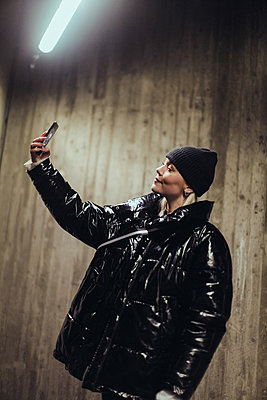 Young woman wearing black shiny jacket while taking selfie with mobile phone against wall in subway - p426m2088916 by Maskot