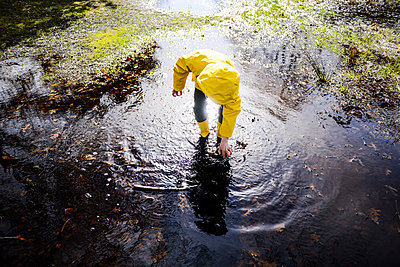 Boy in yellow anorak bending forward in park puddle - p429m1408179 by Bonfanti Diego