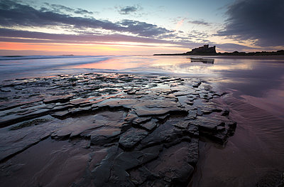 View towards Bamburgh Castle at sunrise from Bamburgh Beach, Bamburgh, Northumberland, England, United Kingdom, Europe - p871m1498191 by Lee Frost