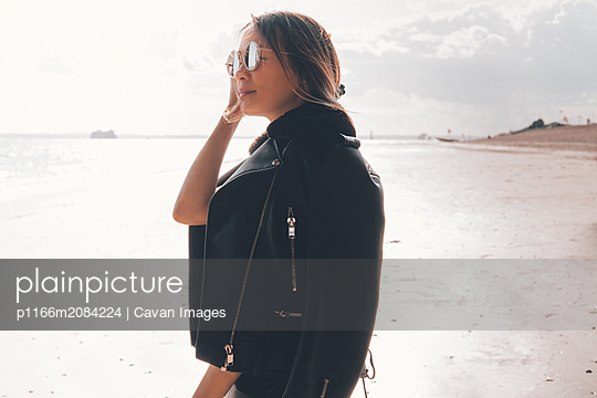 Asian woman wearing sunglasses on the beach - p1166m2084224 by Cavan Images