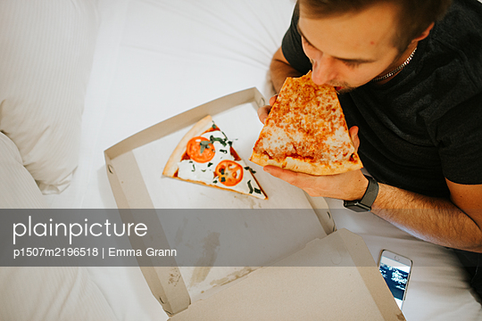 Man eating pizza in bed - p1507m2196518 by Emma Grann