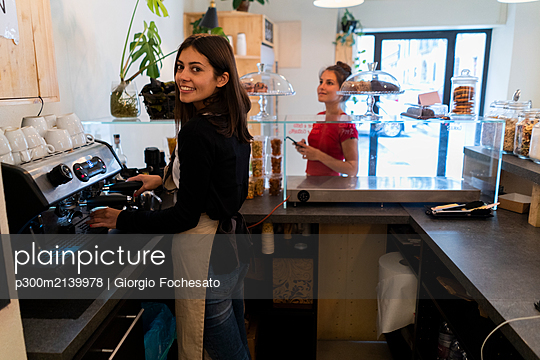 Portrait of smiling young woman preoaring a coffeer in a cafe - p300m2139978 by Giorgio Fochesato