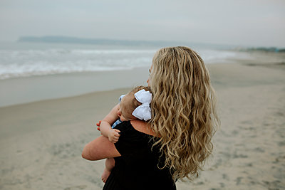 Mother carrying daughter while standing at beach - p1166m1518784 by Cavan Images