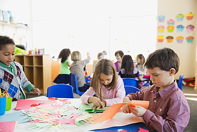 Elementary students tracing hands in class - p1192m1023779f by Hero Images