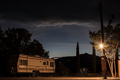 Sunset Behind Mountains With A Wooden Electricity Pylon Light And Electricity Box Attached, Next To A Tree To The Left A Dimly Lit Caravan In Front Of Trees - p1291m1548103 by Marcus Bastel
