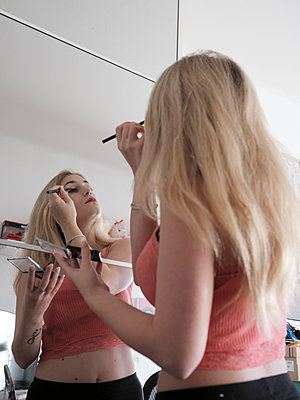 Junge Frau trägt Make-Up auf - p1383m2045097 von Wolfgang Steiner