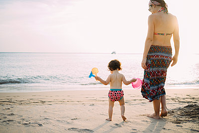 Thailand, Koh Lanta, back view of baby girl and mother on the beach by sunset - p300m2069838 von Gemma Ferrando