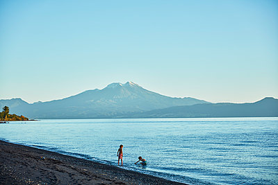 Chile, Lago Llanquihue, Calbuco volcano, two boys playing in water - p300m2070704 by Stefan Schütz