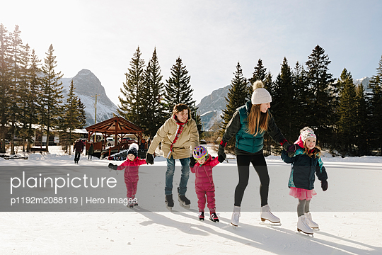Family holding hands, ice skating on sunny frozen pond - p1192m2088119 by Hero Images
