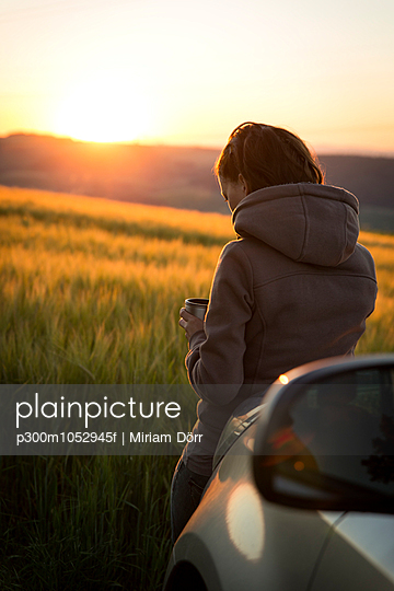 Germany, woman leaning on car in front of a field at sunrise - p300m1052945f by Miriam Dörr