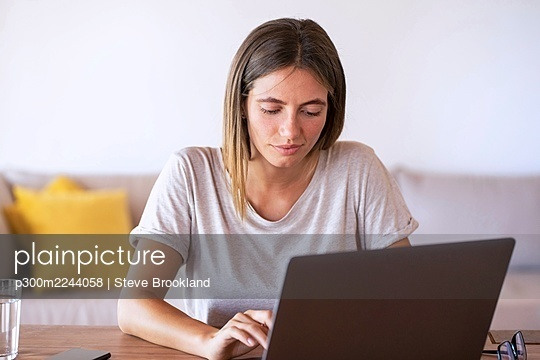 Beautiful female professional using laptop while working at home - p300m2244058 by Steve Brookland