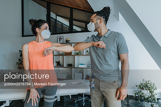 Male physiotherapist and female patient greeting with elbow bump in practice during pandemic - p300m2276794 by Mareen Fischinger