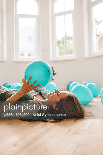 Young woman in new apartment playing with balloons - p586m1064902 by Kniel Synnatzschke