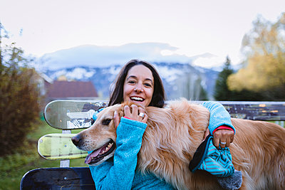 Portrait of cheerful woman with dog sitting on park bench - p1166m1526911 by Cavan Images