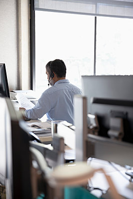 Businessman with headset working in office - p1192m2062433 by Hero Images
