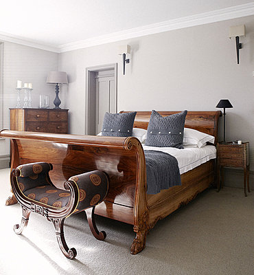 Polished wooden sleigh bed in bedroom of Guildford home - p349m790399 by Brent Darby