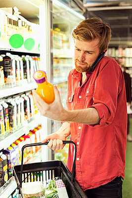 Man answering mobile phone while shopping juice bottle at freezer section in supermarket - p426m1017987f by Maskot