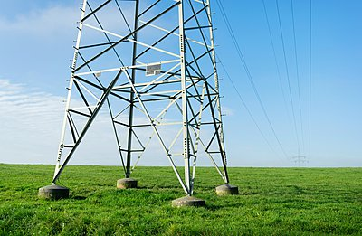Electrical towers and power lines over green field - p429m1103132 by Mischa Keijser