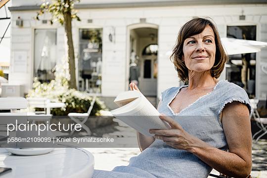 Mature woman reading book in sidewalk cafe - p586m2109099 by Kniel Synnatzschke