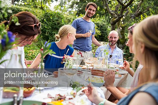 Gemeinsam essen auf einer Gartenparty - p788m1165334 von Lisa Krechting